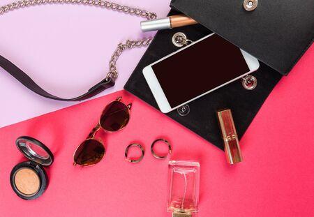 Vista superior del bolso de mujer y cosas de dama con copyspace sobre fondo de color