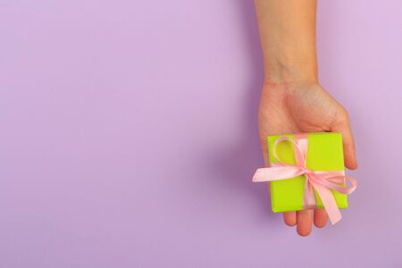 gift in female hands on a colored background top view. Banco de Imagens