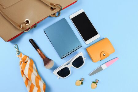 Top view of Women bag and lady stuff with copyspace on blue  background Banco de Imagens