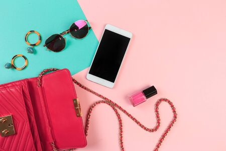 Top view of Women bag and lady stuff with copyspace on pink background