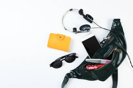 Concetto di moda: lay piatto di borsa donna in pelle si apre con occhiali da sole e smartphone su sfondo bianco.