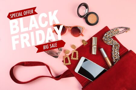 Top view of Women bag and lady stuff with copyspace on pink background. Black friday sale