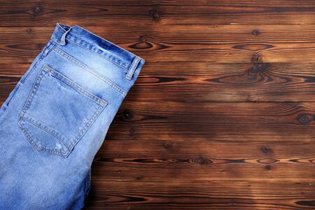 blue denim jeans  on wooden background - Image  Stock Photo