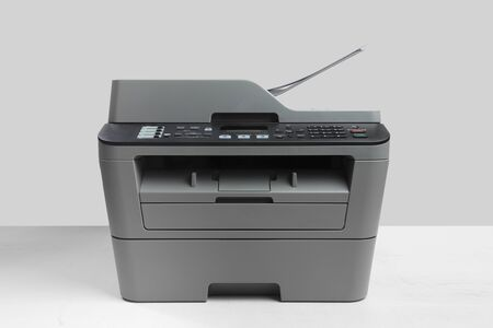 A multi function printer, copier, scanner on office table. gray wall behind
