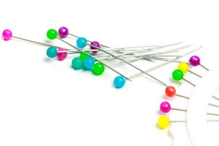 colorful ball point pins in white background
