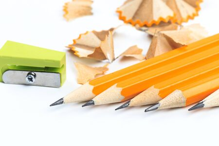 Bunch of yellow pencils with shawings and pencil sharpeners isolated on white