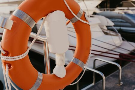 lifebuoy hanging on metal railing, on the background of marina. Sea shore, sunny day, outdoor.