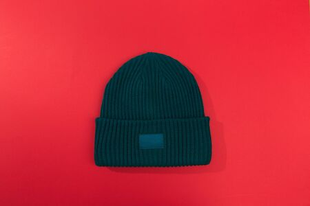 green beanie hat on red  background Imagens