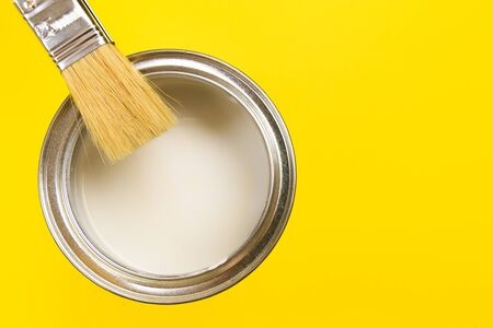 hand holding Brush  on open can of paint on yellow background. Renovation concept