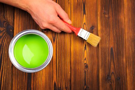hand holding a brush over can of paint on a wooden table 版權商用圖片