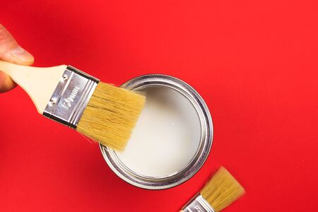 hand holding Brush  on open can of   paint on red  background. Renovation concept