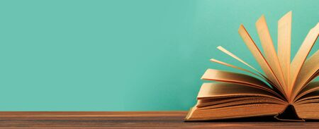 Open book on wooden vintage table blue background - Image
