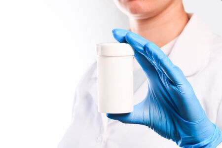 Doctor hand in sterile gloves holding jar with pills isolated on white background