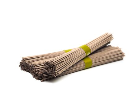 Dried raw japanese soba noodle sticks isolated on a white background.