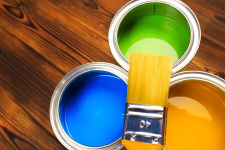 House renovation, paint cans on the old wooden background with copy space