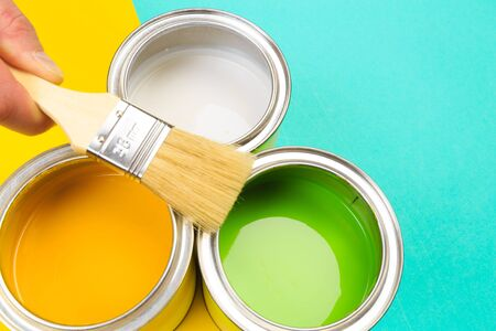 hand holding Brush  on open can of  paint on pastel multicolor  background. Renovation concept