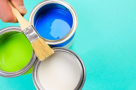 Metal paint cans and hand holding paint brush on color background. Top view. Copy space