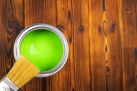 House renovation, paint can on the old wooden background with copy space