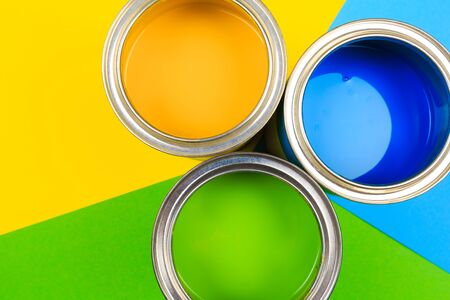 Metal paint cans and paint brushes on multicolor background. Top view. Copy space. 版權商用圖片