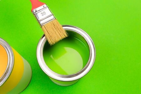 hand holding Brush  on open can of paint on green  background. Renovation concept