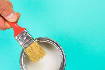 hand holding Brush  on open can of white  paint on pastel blue  background. Renovation concept 版權商用圖片