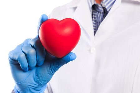 Doctor hand in sterile gloves holding heart  isolated on white background