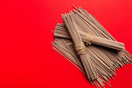 Dried Organic Buckwheat Soba Noodles Ready to Cook on red background