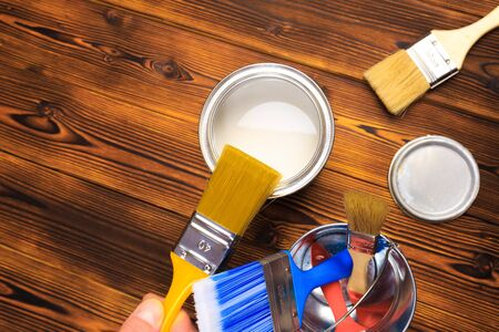hand holding a brush over can of paint on a wooden table Imagens