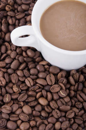 decaf: Cup of coffee sitting in a bed of coffee beans Stock Photo
