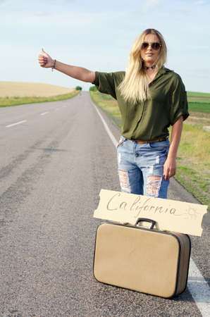 Blonde holding sign while hitchhiking on the road in summertime.