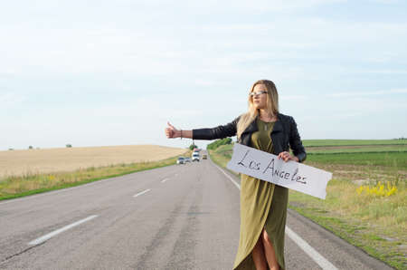 Portrait of a traveling blonde girl who stands by the road. Summer hot time. Reklamní fotografie