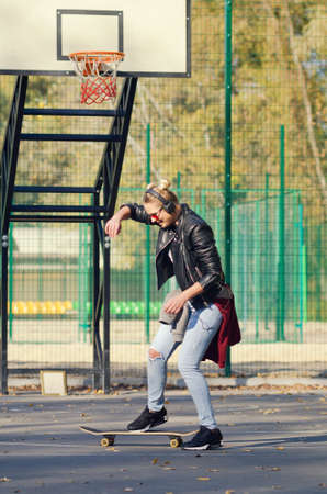 Sensual hipster girl posing with a skateboard on the embankment. Banque d'images - 131764886