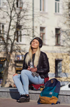 Lady girl happy smiles, sits skateboard, longboard, tanned skin. Emotional joyful. Beautiful european young woman. On the background of the old town.