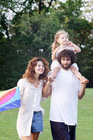 On a sunny warm day, a young family with a daughter have a good time in the park. Reklamní fotografie