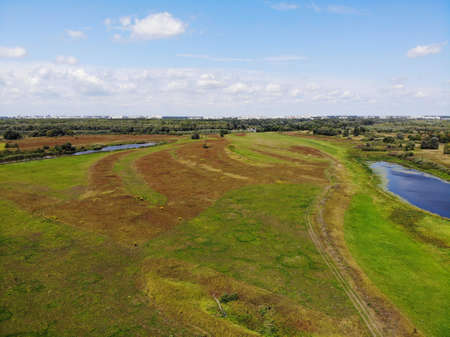 Green beautiful meadows in the river valley. Photo taken from a professional drone.