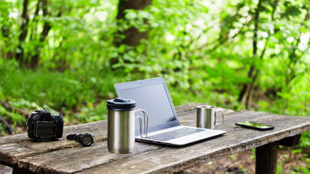 Close-up photo of a laptop, camera, coffee and smartphone on a wooden table outdoors.