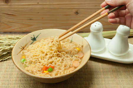 Bowl of instant noodles with carrots and peas on bamboo mats