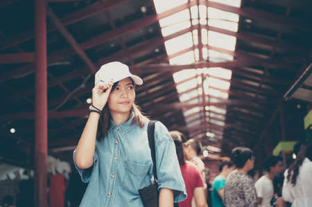 A young woman wearing a hat is walking in the market streets of an asian country,Thailand