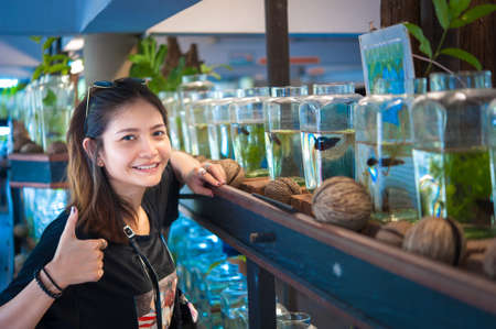 fish tail: A young woman travelerwatching a Fighting Fish in Bottles  at Siamese Fighting Fish Gallery ,Thailand