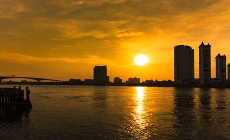 Bangkok City skyscrapers silhouette urban view silhouette of steel bridge over the Chao Phraya River,Bangkok, Thailand at sunrise.