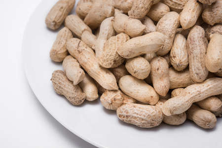 Dried peanuts on white plate at on white background Stock Photo