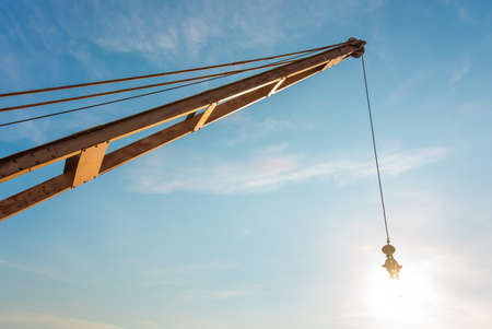 Yellow truck crane boom with hooks and scale weight above blue sky