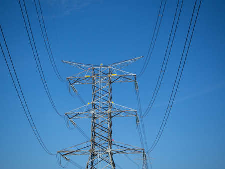 electric grid: a high voltage power pylons against blue sky