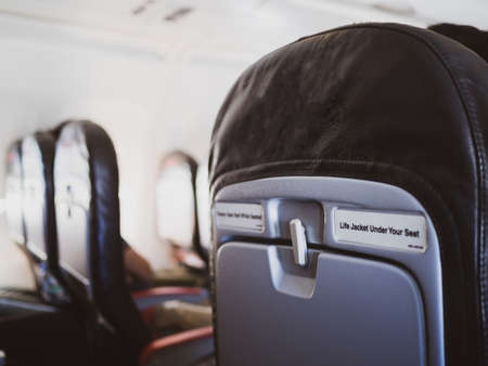 seat rows in an airplane cabin, Interior of commercial airplane with unrecognizable passengers on their seats during flight shot from the rear of airplane.