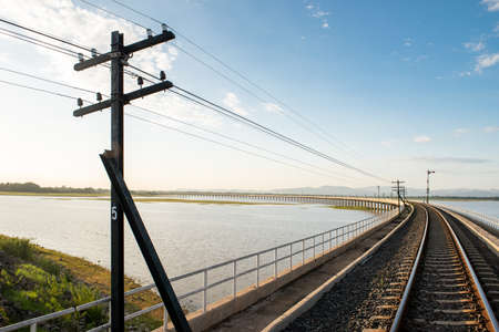 Landscape View of Train crossing Pasak Chonlasit Dam. Reservoir for agriculture at Lopburi, Thailand Stock Photo