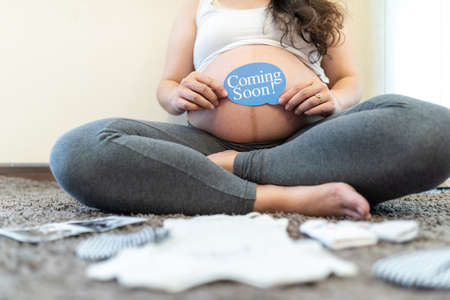 Pregnant woman feeling happy : The young expecting mother holding baby in pregnant belly.