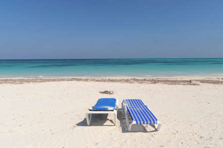 lounger: White tropical beach with two sun lounger in the caribbean, Cuba. Stock Photo