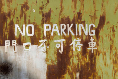 old english letters: Old door with  letters NO PARKING in English and Chinese  language .