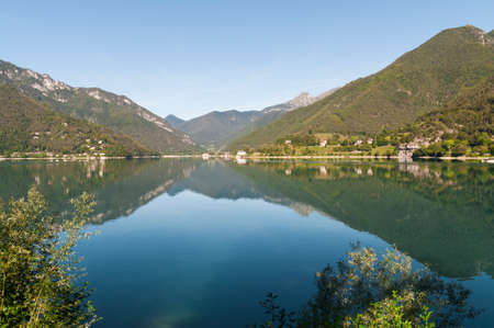 mirrored: Mountain panorama mirrored of lake ledro in north Italy. Stock Photo
