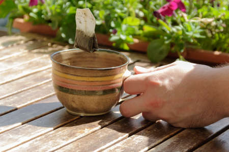 teabag: Human hand hold a cup with teabag . Stock Photo